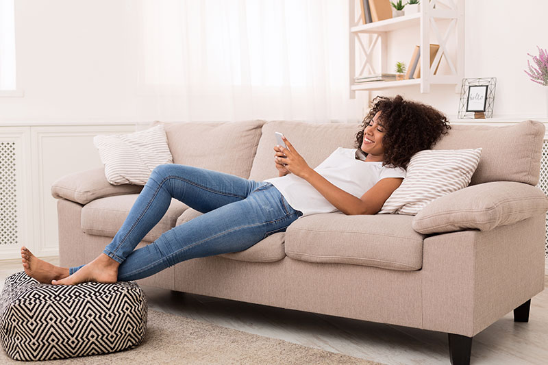 Junge Frau, die gerade auf dem Sofa liegt und auf dem Smartphone eine Landingpage betrachtet.